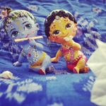 adorable radha and Krishna dolls Krsna has flute and Radha has flower, sitting on an ikat sarong in beautiful boho blue with bouganvillia flowers