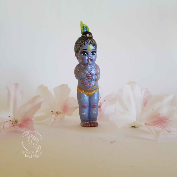 Gopal krishna doll standing among white azaela flowers on a white backdrop wearing a peacock feather and looking like trouble and mischeif