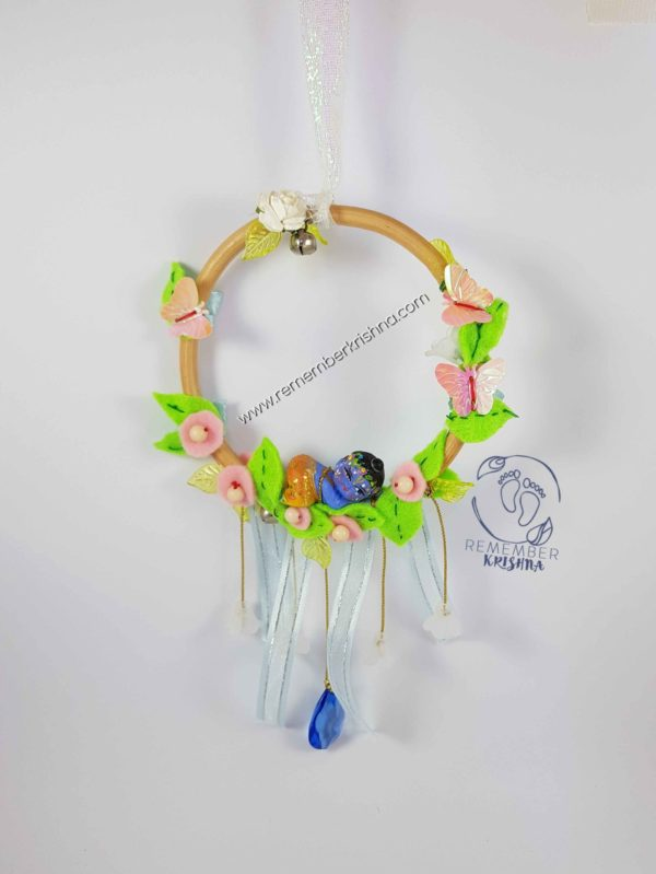 darling baby krsna doll nestled into leaves in a wooden hoop with a hanging blue jewel and sweet suspended flowers, pastel pink and leaves for wind chime which dangles like a dreamcatcher
