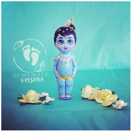 Krishna stands on blue background with yellow paper flowers is a doll for sale