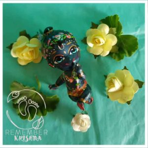 syamasundar Krishna_doll black skinn krsna doll for sale with lotus garland flower crown sitting on a turquoise background with yellow paper flowers around him for kids fun
