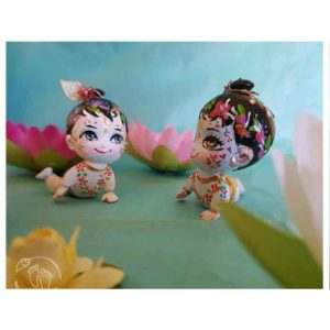 krishna balaram crawling dolls on a turquoise background with lotus flowers
