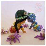 Radharani gazes lovingly at krsna radhe doll krishna doll pair for children with minature purple lotus flowers on pink background