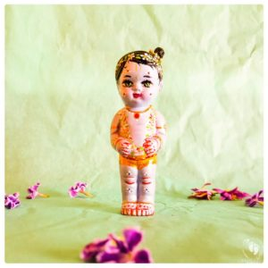 sweet Krishna standing sweetly with garlands of flowers and a little top knot