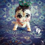 Crawling Krishna with wide eyes and peacock feathers tilak and light blue
