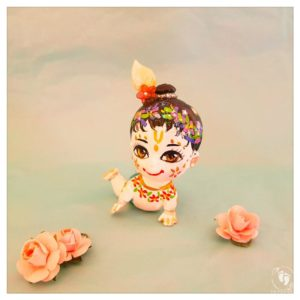 Crawling white skinned balaram doll with bun flower garlands and crawling on hands knees blue background with paper pink roses