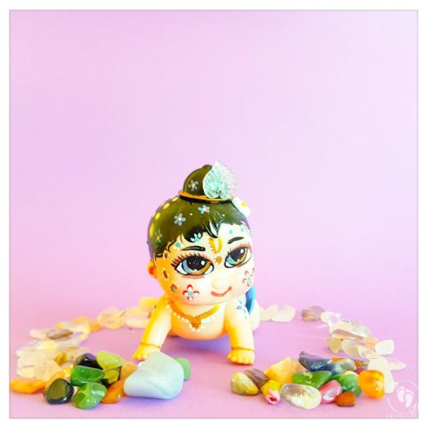 wind up balaram doll toy for kids vaishnava devotees white skin ostritch feather decorations and sitting on purple background with gemstones around.