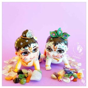krsna and balaram chubby cute wind up toy dolls crawl along on a purple background with gems