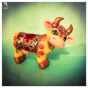little cow krishnas friend handprints decorated blanket golden horns and flowers friendly face