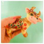 little cow krishnas friend handprints decorated blanket golden horns and flowers friendly face