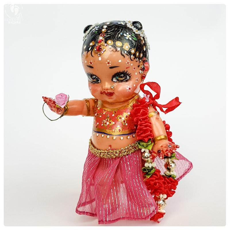 tall radha doll made from plastic with pink clothes and a garland for krsna doll