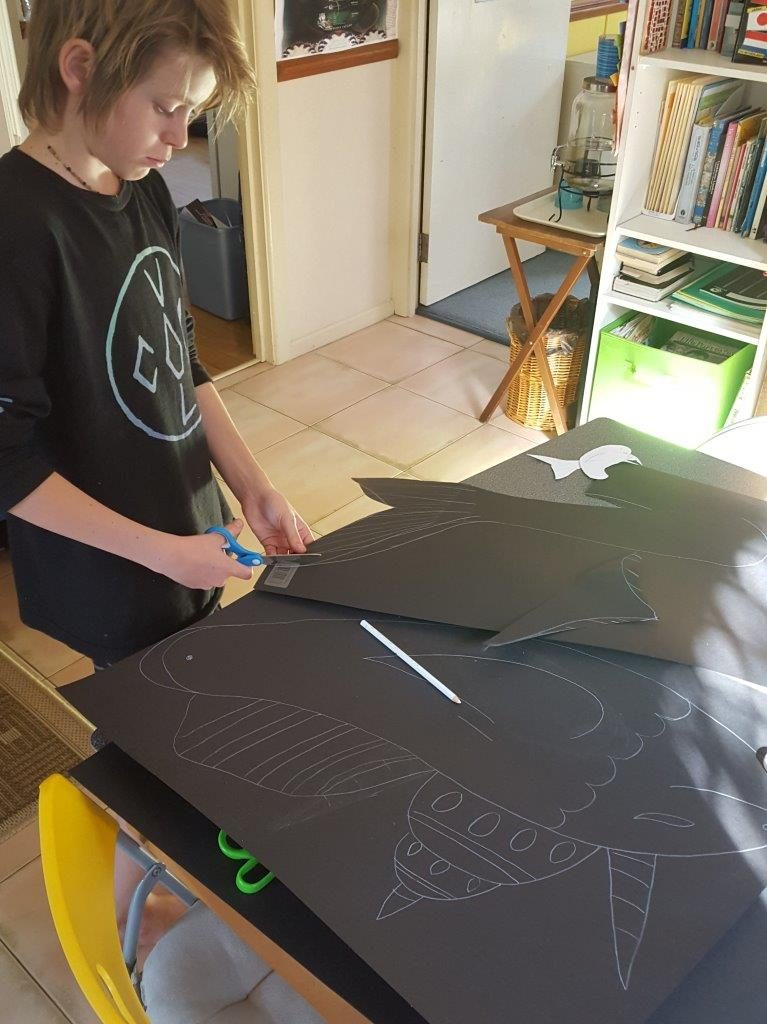 cutting out the silhouette shadow puppets and drawing them before hand kid in shirt and black cardboard
