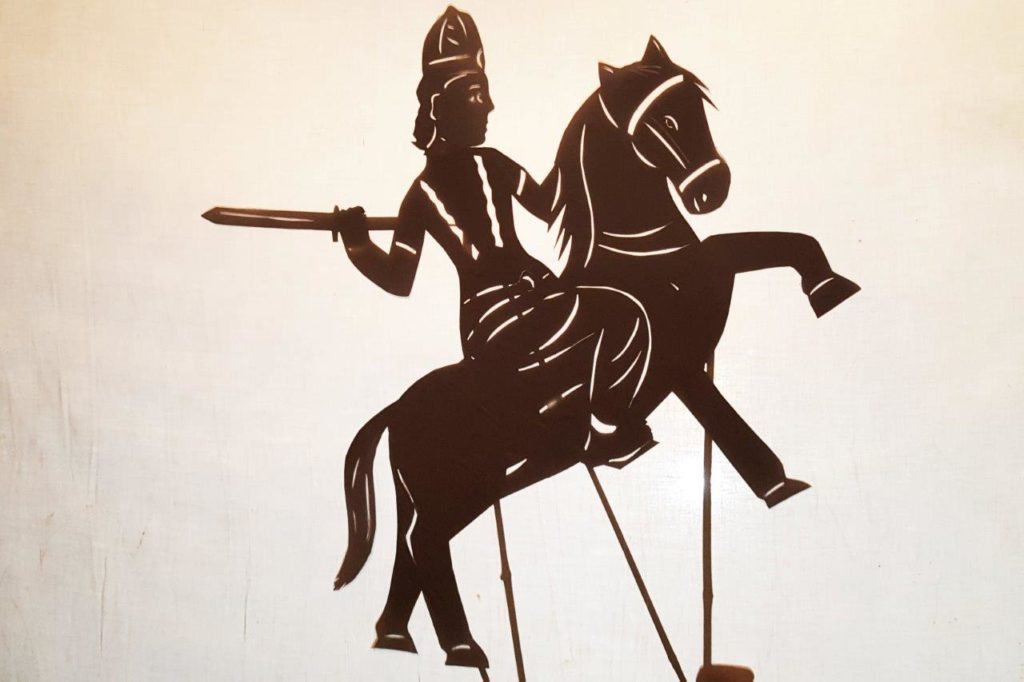 kalki on horse rearing ready to slay demons shadow puppet silhouette
