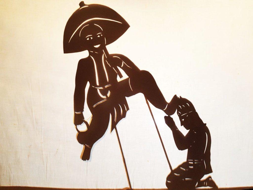Vamana incarnation of Vishnu shadow puppet silhouette placing foot on Bali Maharaj head