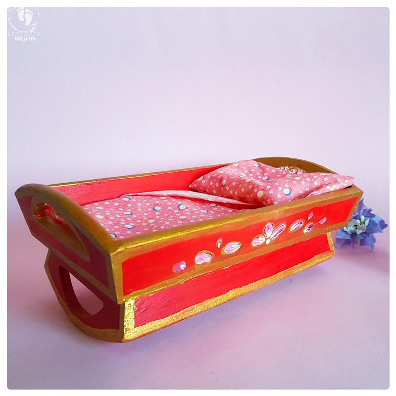 Baby krsna doll blue boy krsna tucked into a wooden rocking cradle painted red with folkstyle art flowers in gold on the sides of the cot and a pink sheet
