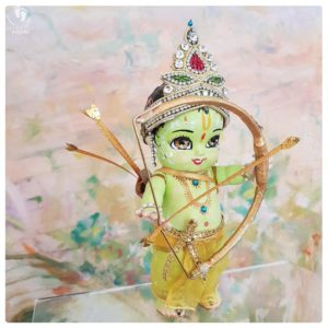 Rama doll for sale lord rama dolls with green skin and golden bow, a golden quiver and a golden arrow strung to rama bow. on a muted peach background. Hindu Vaishnava ramayan interest