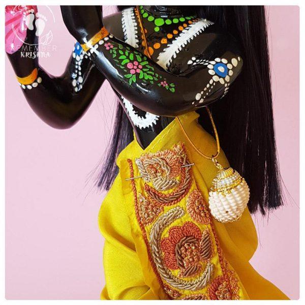 accessory for krsna deity conchshell strung on elastic thread worn by krishna deity