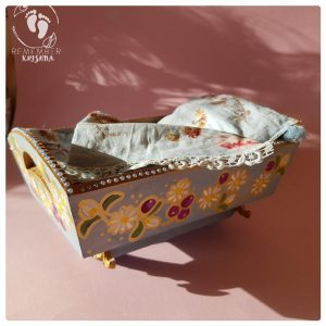 rocking cradle for Krsna dolls painted blue with daisy and blueberry folk art style and blue flowery bedding wooden cradle on pink background