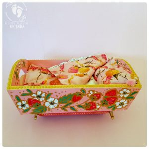 rocking cradle painted pink with strawberries gold highlights and green leaves indian folk art style on wooden cradle pink background