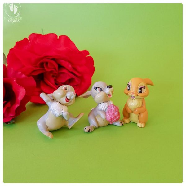 Krishna bunny rabbit friends toys on a green background with red fake roses