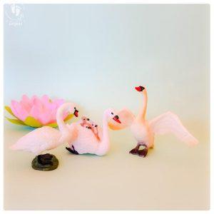 set of three swan dolls toy friends of Krishna plastic swan animals on a aquamarine background
