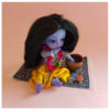 Oriental rug with Krsna doll sitting on rug having a picnic cupcake