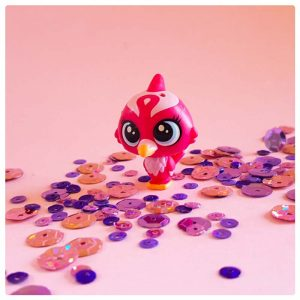 red robin toy bird friend of krishna on a pink background with purple sequins
