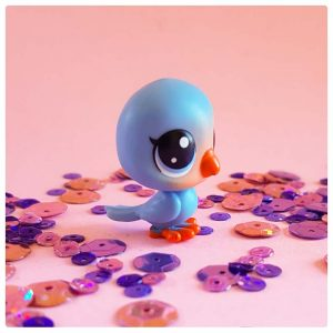 rosy little blue bird on a pink background of sequins